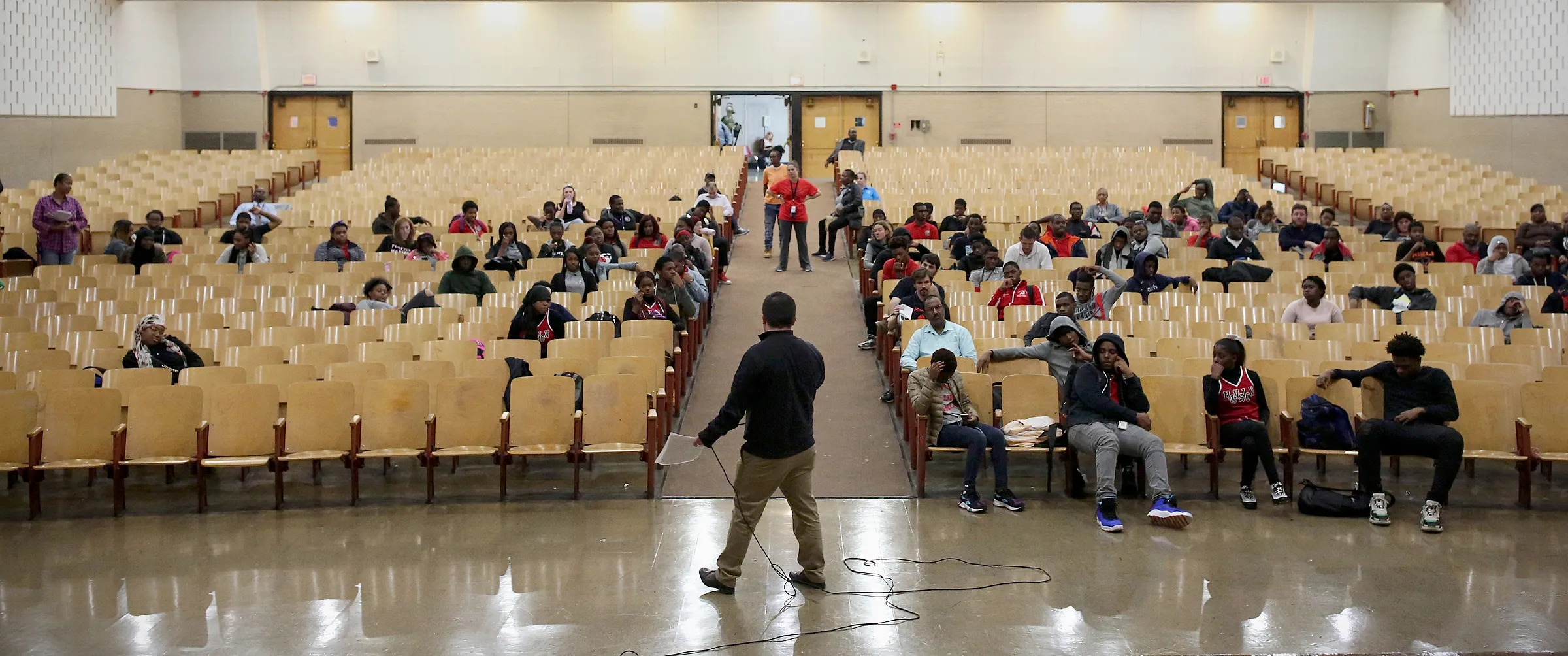 """Principal Brian McCracken, center, speaks during a monthly, schoolwide """"town hall"""" assembly at Strawberry Mansion High School in Philadelphia on Friday, Nov. 2, 2018. Some of the school's seniors were not present because they had early dismissal."""
