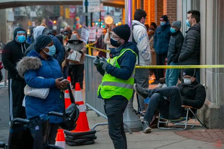 People wait at 12th and Race Streets, outside the Pennsylvania Convention Center, Wednesday as the city began accepting walk-ins for vaccination. Residents from 22 under-vaccinated zip codes in the city were able to walk up and wait in line with a vaccine instead of making appointments online.