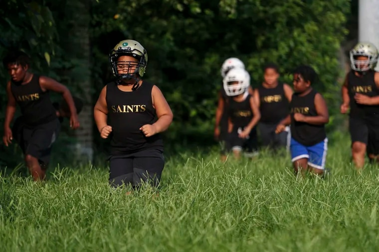 The Parkside Saints youth football team runs laps through overgrown grass on the fields behind the Tustin Recreation Center in Overbrook. The city of Philadelphia's Rebuild program has plans to build a new artificial turf field and stadium on a portion of Edgely Field in West Fairmount Park.