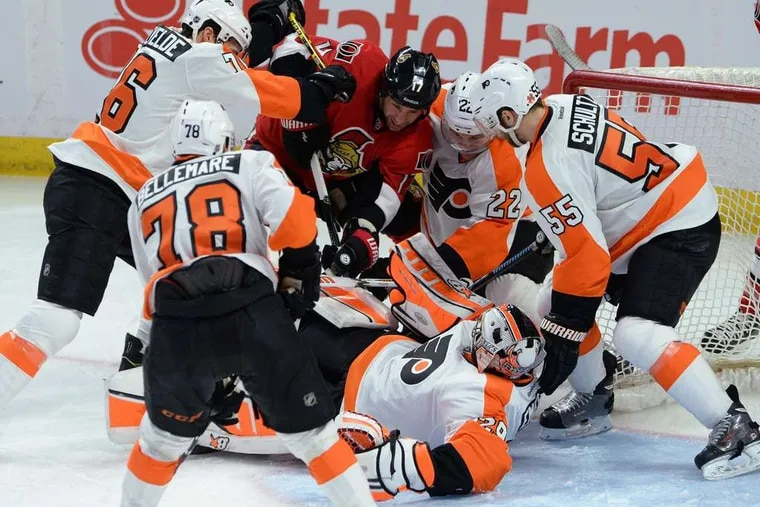 Ottawa's David Legwand is surrounded by Flyers, including goalie Ray Emery, as he fights for the puckin front of the net. The Flyers slipped to 9-18-9 on the road this season.