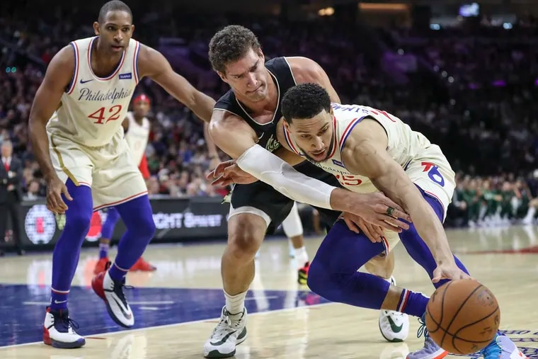 Ben Simmons battles for a rebound against Brook Lopez of the Milwaukee Bucks in the second quarter of a game at the Wells Fargo Center  on Wednesday.