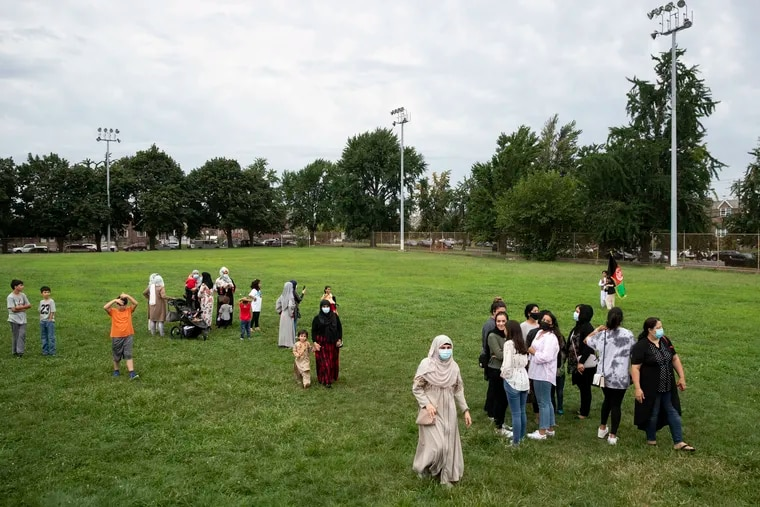 Women and children walk in the grass after a rally in solidarity with the people of Afghanistan and the Afghan community in Philly at Tarken Recreation Center in Northeast Philadelphia on Sunday, Aug. 22, 2021.