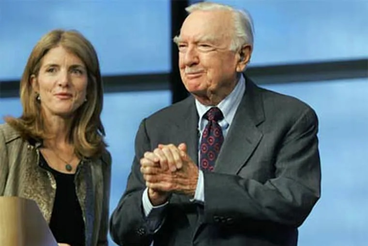 Newsman Walter Cronkite, center, acknowledges cheers from an audience as Caroline Kennedy, left, looks on at the John F. Kennedy Library in 2005. The legendary broadcaster died Friday at age 92. (AP Photo / Steven Senne)