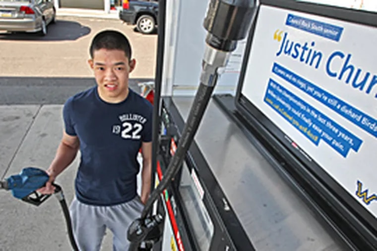 """""""It's like I'm famous,"""" says Justin Chung, at a Penndel pump with a Wilkes ad featuring him. (Michael Bryant/Inquirer)"""