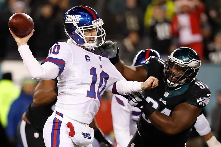 Fletcher Cox grabs the Giants' Eli Manning.