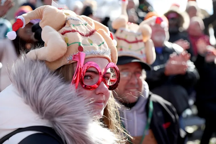 Spectators Chloe Kramer, 16, left, and her dad, Mike, of Willow Grove, watch the 6ABC Dunkin' Thanksgiving Day Parade in Philadelphia, PA on November 28, 2019.