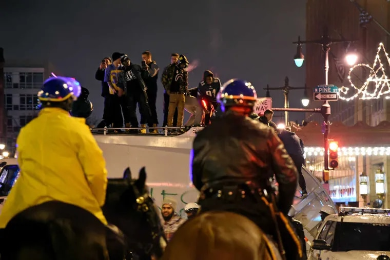 Police on horseback watch as revelers climb on a city garbage truck early February 5, 2018, celebrating at Broad and Pine streets after the Eagles won Super Bowl LII.
