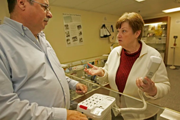 Donald Cassidy shares what he knows about a product at the Sight Solutions store with customer Patty Guarini.