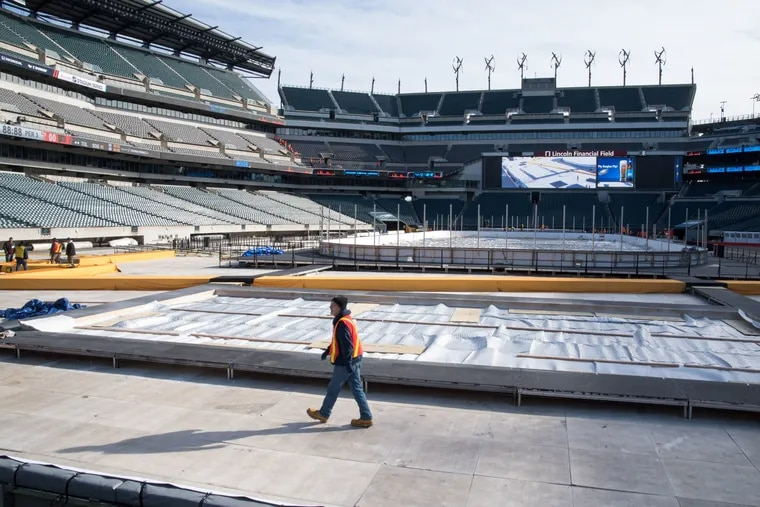 A worker on Tuesday strolls past the rink at Lincoln Financial Field that will host the Flyers and Penguins one of these days this weekend.