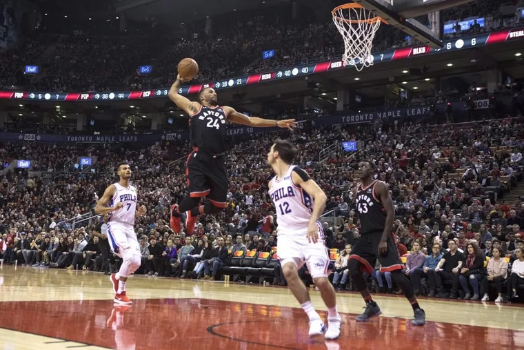 Toronto Raptors' Norman Powell (24) dunks on the Philadelphia 76ers during the second half of an NBA basketball game in Toronto on Saturday, Dec. 23, 2017.
