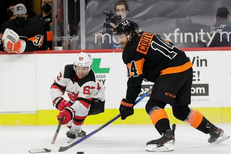 Flyers center Sean Couturier battles for the puck against New Jersey Devils left winger Jesper Bratt during overtime on April 25, 2021. He signed an eight-year extension Thursday.