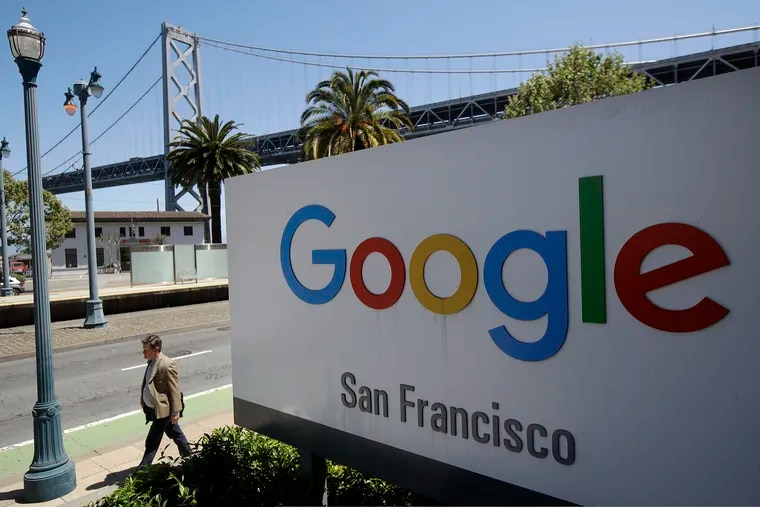In this May 1, 2019 photo, a man walks past a Google sign outside with a span of the Bay Bridge at rear in San Francisco. Over 90 percent of web searches involve a Google platform, so small businesses have to go through the online giant to get noticed. (AP Photo/Jeff Chiu, File)