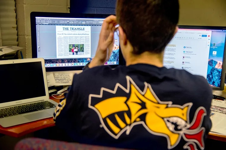 Assistant news editor Ethan Hermann works on the front page layout of the current edition in the newsroom of The Triangle, Drexel's student newspaper. The paper had to stop publishing for a week due to finances, but were able to resume after collecting more than $15,000 in donations.