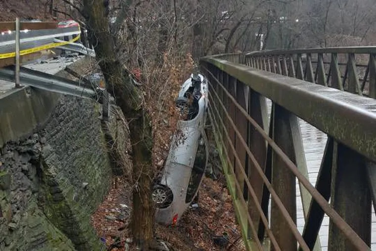 """A car stands upright on the wrong side of a Lincoln Drive guard rail, leaning against an elevated section of the Wissahickon Bike Trail. Philadelphia Streets Department has touted the $12 million Lincoln Drive project as part of its increased """"Vision Zero"""" initiative."""