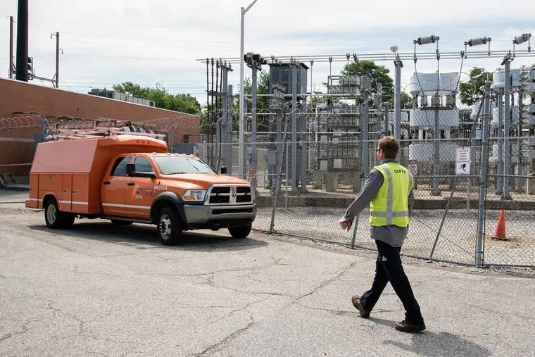 Donates Avizienis walks by the substation through which power provided by Peco would be replaced by electricity produced from a proposed power plant near SEPTA's Wayne Junction station.