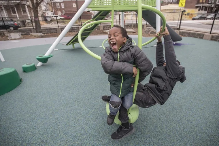 Attim Roseborough, 7, center, is all smiles as his brother, Steven Roseborough, 11, spins them in circles Sunday afternoon at the Conestoga Community Park in Philadelphia.