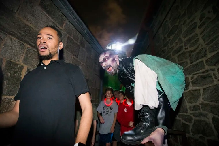 Peter Corbett, right, one of the actors in a Terror Behind the Walls at the Eastern State Penitentiary leaps up on a fence to scare groups. He is shown on Oct. 10, 2018.