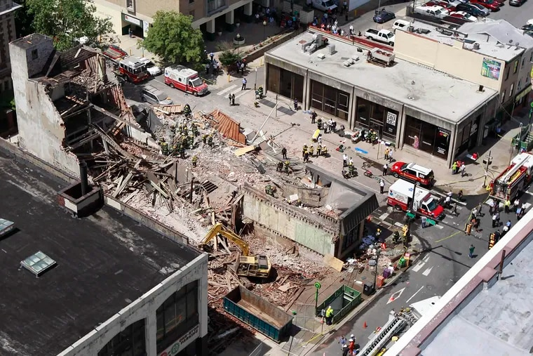 Firefighters remove debris by hand after a collapse at 22nd and Market. ( DAVID SWANSON / Staff Photographer )