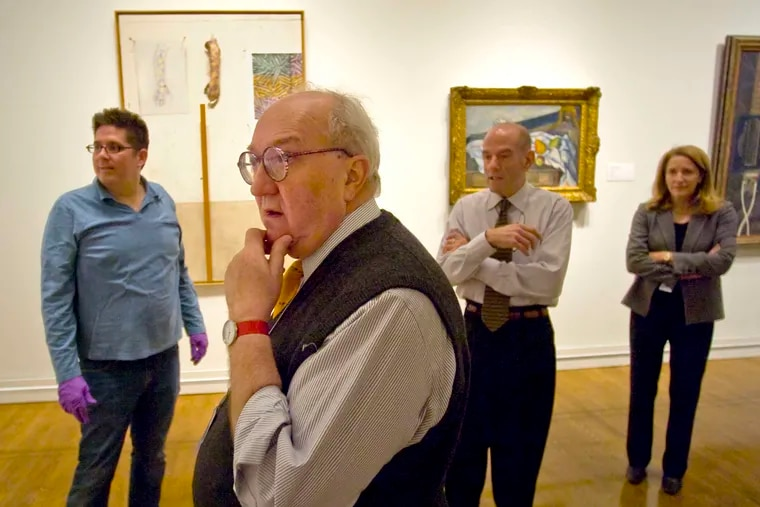 Joseph Rishel checking whether a Cézanne work hangs properly in a 2009 exhibit.