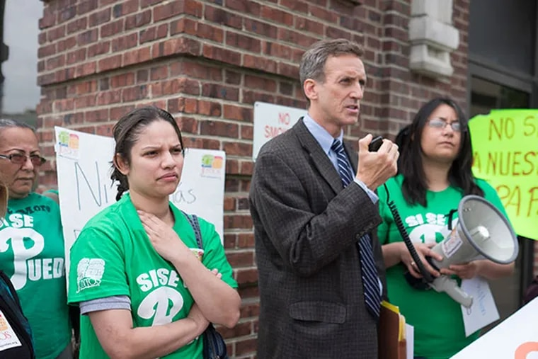 Pilar Molina, left, wife of jailed Israel Resendiz Hernandez, listens as attorney Thomas Griffin alms about the family's plight during a small rally held outside the US immigration offices, Wednesday, May 7, 2014.  (ED HILLE / Staff Photographer )