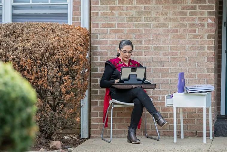 Perla Lara se sienta en su área de trabajo fuera de su apartamento, mientras coordina la próxima edición de Impacto.