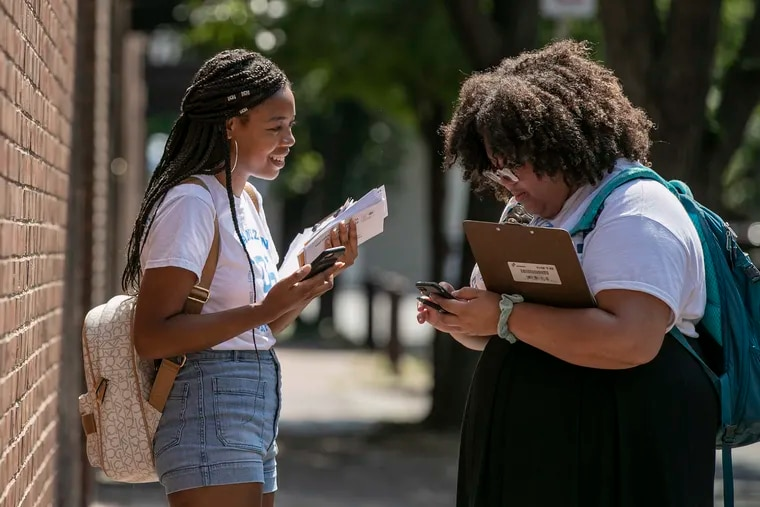 Alexis Perry (left), 21, and Danielle Foltz, 20, canvass for judges on the ballot in November, as part of the DNC's Organizing Corps 2020 initiative, in Old City Philadelphia last month.