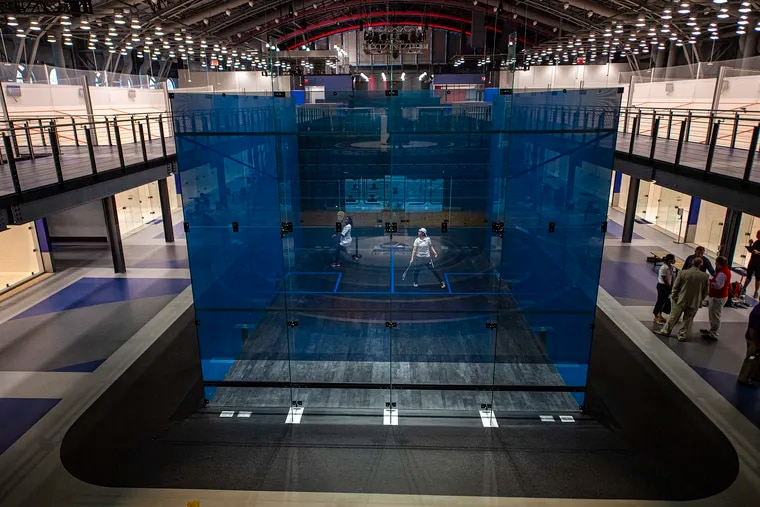 DuBois Stewart (left) and Kat Burgos, from the SquashSmarts program, play in the glass court at the center of the new Arlen Specter US Squash Center. The facility was inserted into a historic armory on 33rd Street, near the Drexel University campus.