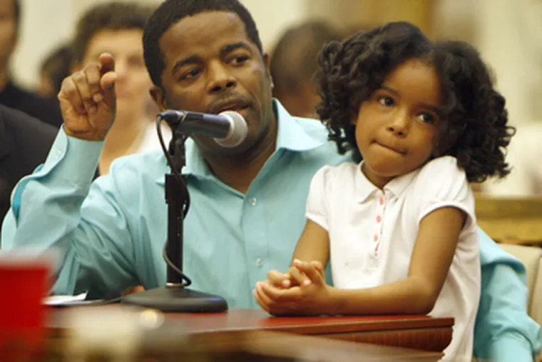 First grader Elshadye Bussie listens as her father, Emmanuel, urges City Council not to cut school funding and programs. (David Maialetti / Staff Photographer)