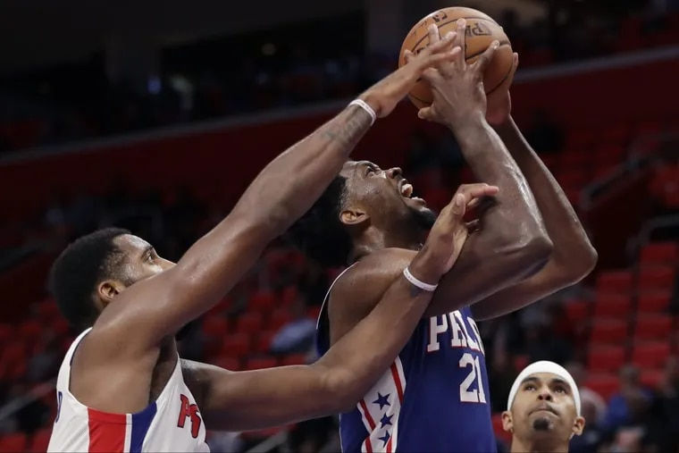 Joel Embiid (21) shoots as Pistons center Andre Drummond reaches in during the second half Monday night.