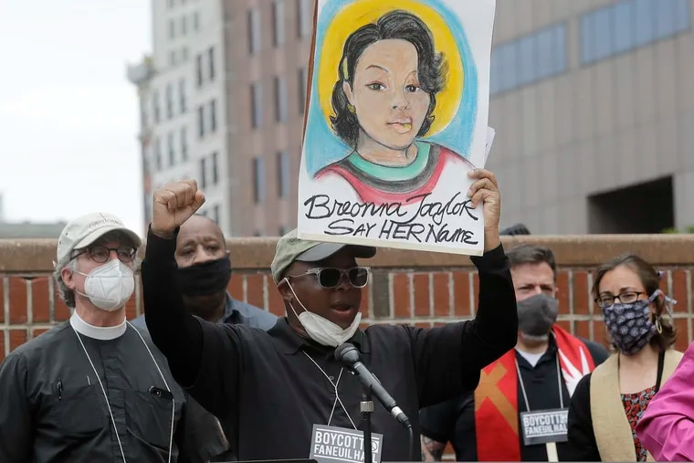 Kevin Peterson, founder and executive director of the New Democracy Coalition, displays a placard showing Breonna Taylor as he addresses a June 9 rally in Boston. Petersen advocates for changing the name of Faneuil Hall, as its namesake Peter Faneuil was an enslaver.