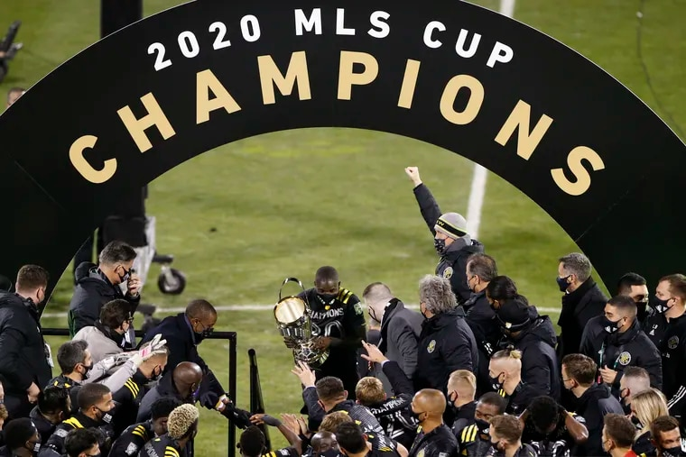 Columbus' Jonathan Mensah carries the trophy on stage after the Crew defeated the Seattle Sounders 3-0 in the MLS Cup championship game.