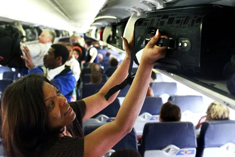 Southwest Airline passenger Robin Bonner, of Solon, Ohio, places her luggage into the overhead compartment on a flight from Midway Airport in Chicago to Cleveland, Ohio, April 2, 2010.
