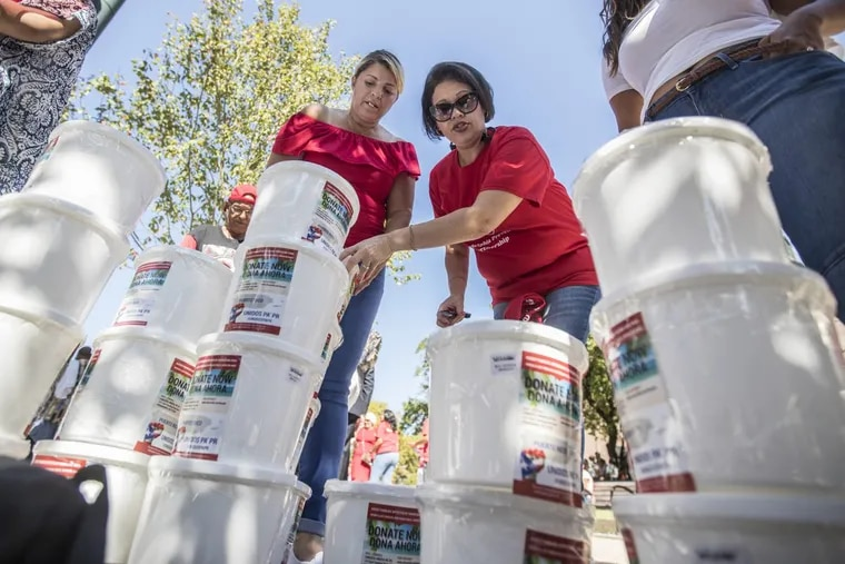 Reverend Jessie Alejandro (left) and Madeline Neris-Negro of Unidos Pa' PR stack up the plastic donation buckets used during Sunday's Puerto Rico Day Parade to solicit money for the island after the devastation of Hurricane Maria.
