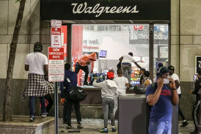 People jump through the broken window at Walgreens at Broad and Chestnut streets in  Center City Philadelphia, Saturday,  May 30, 2020. Thieves stole filled prescriptions and paper records with health information from Walgreens stores nationwide between May 26 and June 5, the company disclosed.