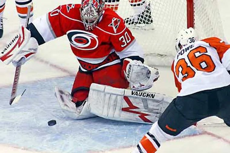 Hurricanes goalie Cam Ward tries to control the shot of Flyers' Darroll Powe during the first period. (AP Photo/Karl B DeBlaker)