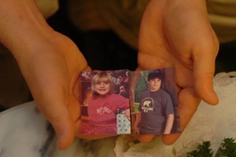 Charles Bennett displays photographs of two of his grandchildren - Melanie (left), 6, and Scottie, 12 - who were murdered by their father in May 2006.
