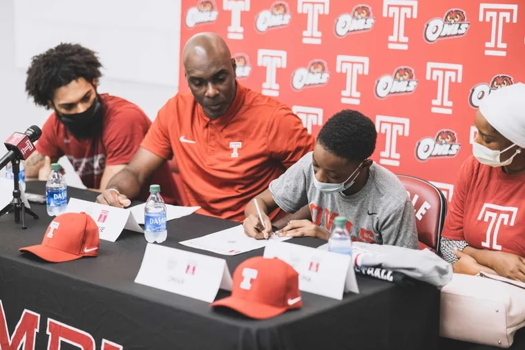 Omar Singhateh, a 15-year-old with sickle-cell anemia, was added to the Temple roster as part of Team IMPACT. Here, he signs on the dotted line.