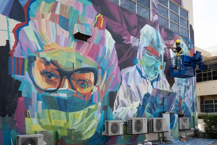 A worker gave final touches to a graffiti that tributes to Malaysian workers on the frontline against the COVID-19 pandemic outside a hospital in Kuala Lumpur, Malaysia, Friday, Jan. 29, 2021. The pandemic has produced many surprises. (AP Photo/Vincent Thian)