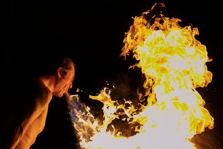 """A performer spits fire during the """"Ghostly Circus: Tides of the Climate"""" show at Laurel Hill Cemetery in Philadelphia on Friday, Aug. 09, 2019."""