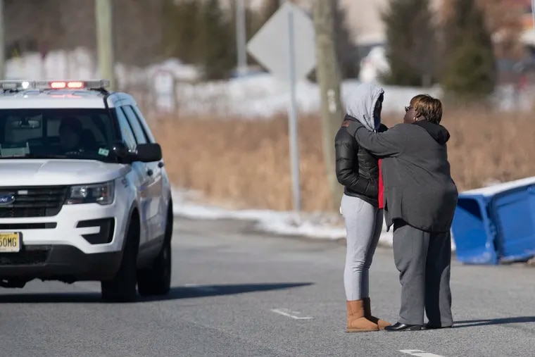 Two unidentified women were seen consoling each other at a police checkpoint on Jan. 14, 2019, after a report of an active-shooter situation that morning at a UPS facility in Logan Township, South Jersey.