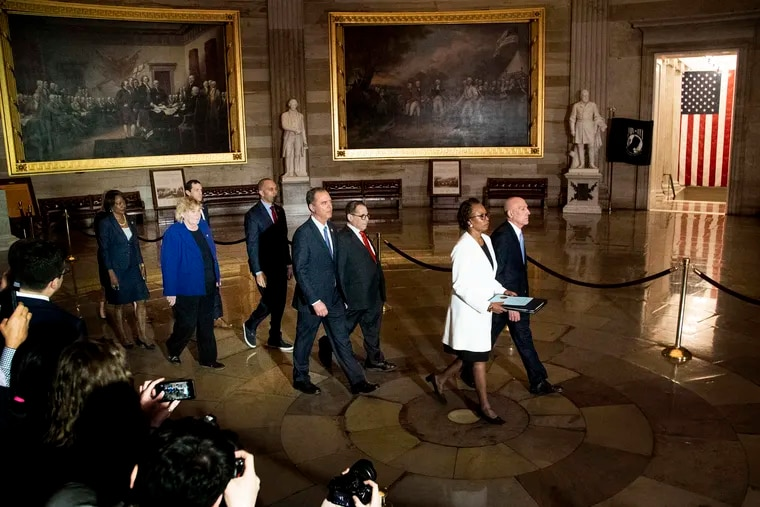 Leading the way to deliver the articles of impeachment to the Senate are Paul Irving (right), House sergeant at arms, and Cheryl Johnson,clerk of the House. Behind them, in a solemn procession, are the designated impeachment managers.