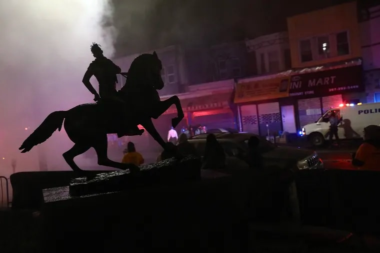 Smoke from a burning trash bin silhouettes a statue by Kehinde Wiley at 52nd and Chestnut Streets in West Philadelphia.