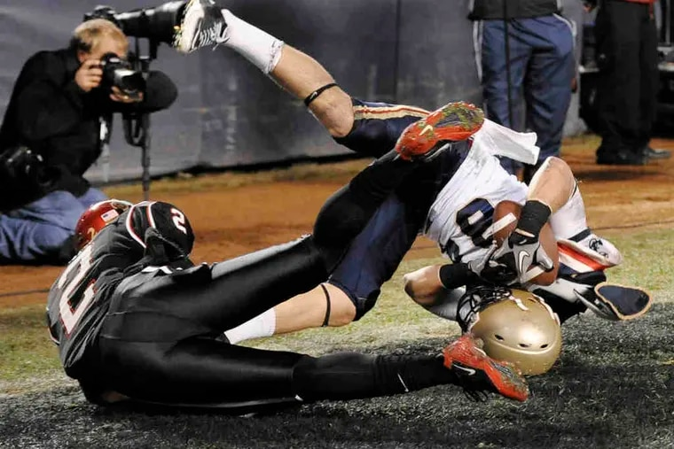 Navy's Greg Jones makes a tumbling, 30-yard touchdown catch in front of San Diego State's Leon McFadden. The Aztecs took a 21-14, halftime lead in Thursday's Poinsettia Bowl.