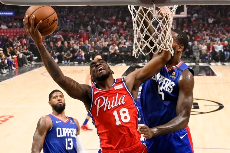 76ers guard Shake Milton shoots as Clippers forward JaMychal Green (right) defends and guard Paul George watches during the first half in Los Angeles.