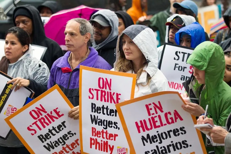 At City Hall, signs were in both English and Spanish. Tuesday's rain left participants soggy. The push for a higher minimum wage has more support among Democrats than Republicans.