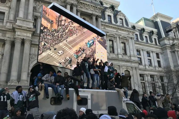 Eagles fans climbed the Jumbotron TV at City Hall to get a better vantage point on the team's Super Bowl victory parade.