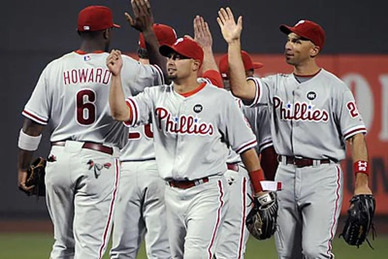 Phillies players celebrate their 6-3 win over the Mets. (Bill Kostroun/AP)