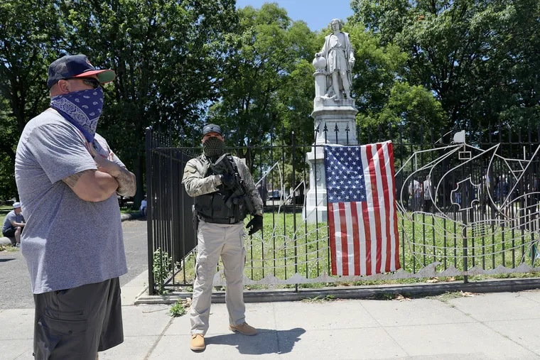A man who didn't want to be identified carries a rifle as he and others stand in front of the Christopher Columbus statue at Marconi Plaza in South Philadelphia on Saturday. Dozens of South Philadelphia residents came out Saturday to defend the statue after hearing social media rumors that protesters could try to damage it.