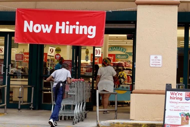 "A ""Now Hiring"" sign hangs near the entrance to a Winn-Dixie Supermarket in Hallandale, Fla."
