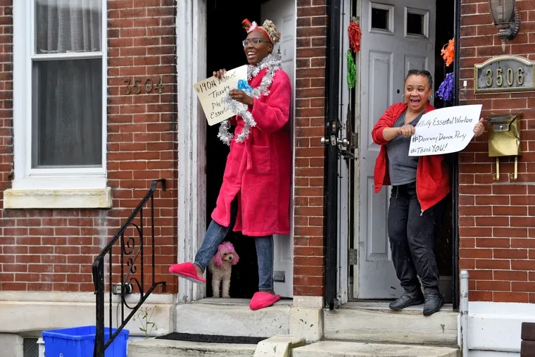 Shelia Simmons (right) and her neighbors including Onisha Claire (with dog Lucy behind the slippers) step out Wednesday during the Philadelphia citywide Doorway Dance Party for essential workers she is organizing.